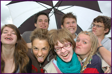 7 young people pulling faces under an umbrella